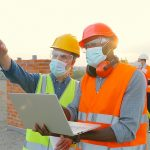 Group Of Builders In Hardhat Works On The Building Site. Two Mal